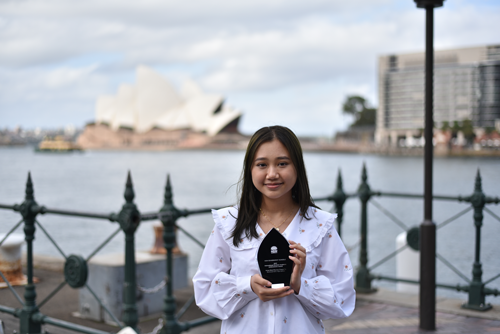 Girl with and award in front of the Sydney Opera House