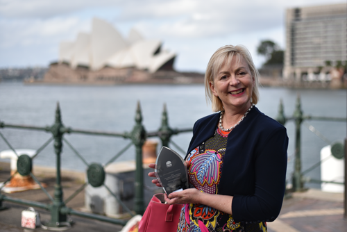 Female with and award in front of the Sydney Opera House